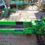 Photo of stationary electric wood grinder with infeed conveyor installed at a sawmill.
